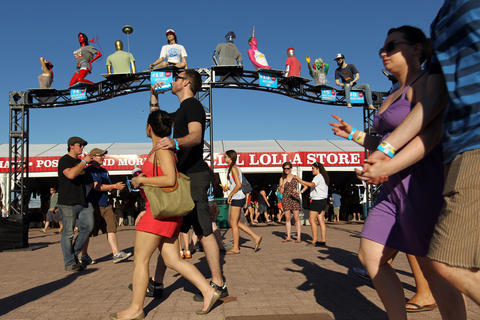 Fest goers walk by the Lollapalooza store in Grant Park in Chicago on Sunday, August 5, 2012.