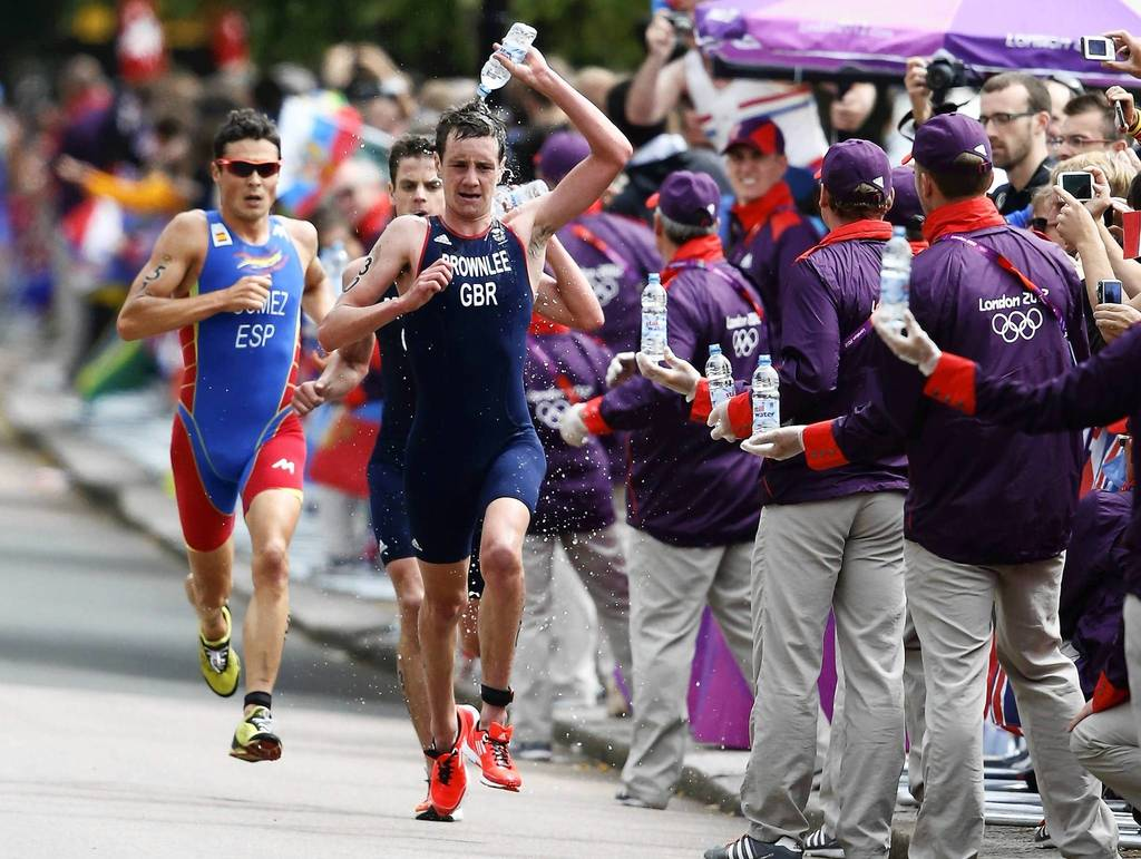 Britain's Alistair Brownlee, right, pours water over his head as he runs ahead of Jonathan Brownlee, center, and Spain's Javier Gomez in the Men's Triathlon final during the London 2012 Olympic Games.