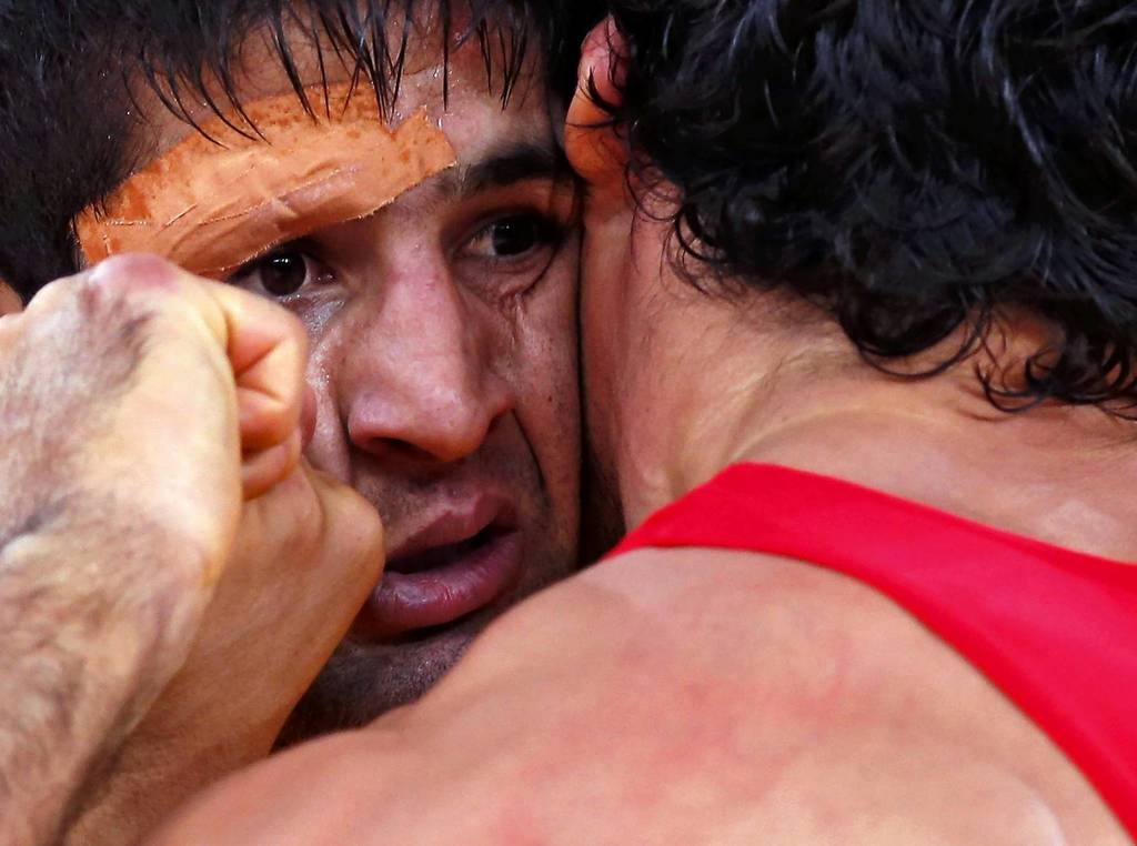 Iran's Saeid Morad Abdvali, left, fights with Turkey's Atakan Yuksel on the Men's 66Kg Greco-Roman wrestling at the ExCel venue during the London 2012 Olympic Games.