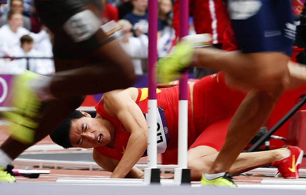 China's Liu Xiang falls after hitting a hurdle in his Men's 110m Hurdles round 1 heat during the London 2012 Olympic Games at the Olympic Stadium.