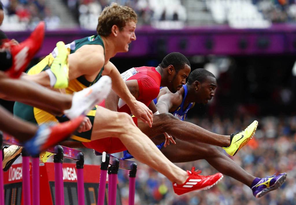 Jeff Porter, center, of the U.S., clears a hurdle in his Men's 110m Hurdles heat during the London 2012 Olympic Games at the Olympic Stadium.