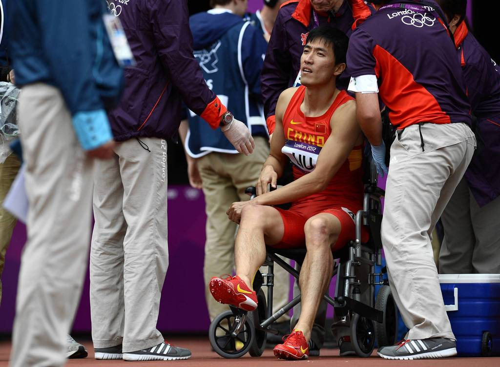 China's Liu Xiang, surrounded by medics, sits in a wheelchair after falling in one of the Men's 110m hurdles heats at the London 2012 Olympic Games.