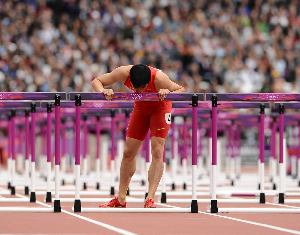 Xiang Liu (CHN) kisses a hurdle after falling in his Men's 110m hurdles heat during the London 2012 Olympic Games.