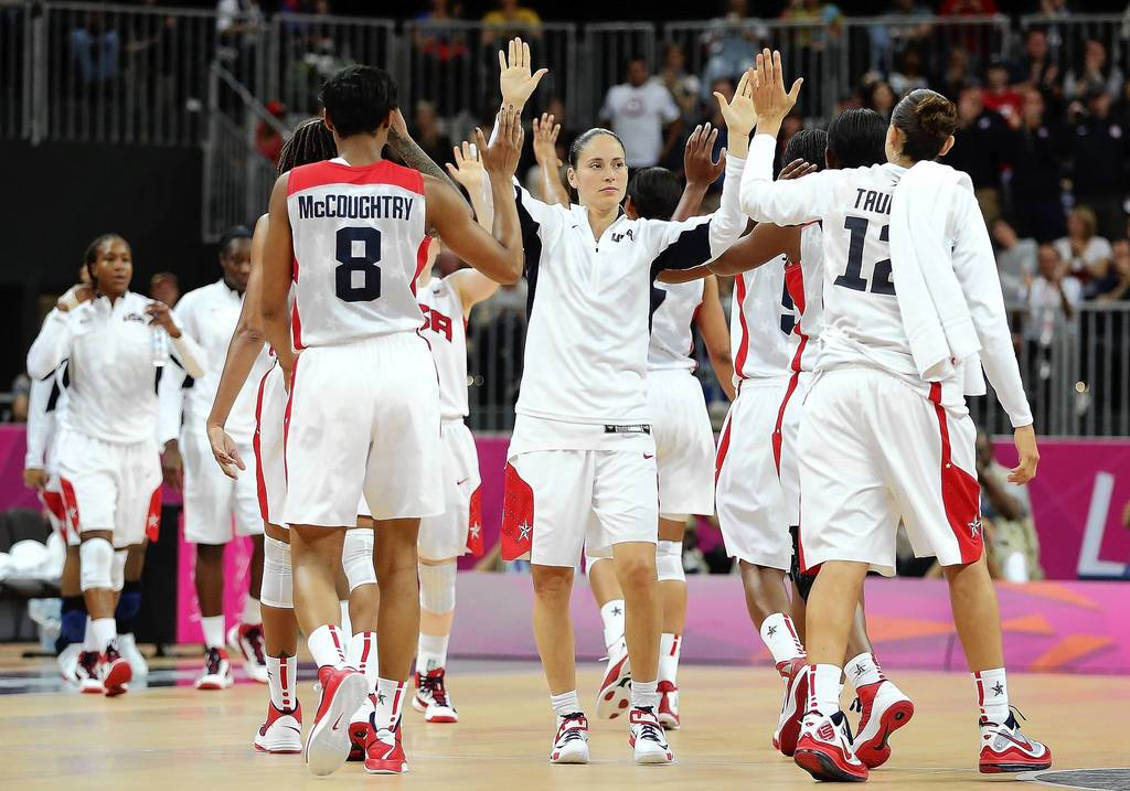 Sue Bird, center, high fives U>S. basketball teammates Angel McCaughtry, left, and Diana Taurasi, right, after defeating Canada 91 - 48 in the Women's Basketball quaterfinal on Day 11 of the London 2012 Olympic Games.