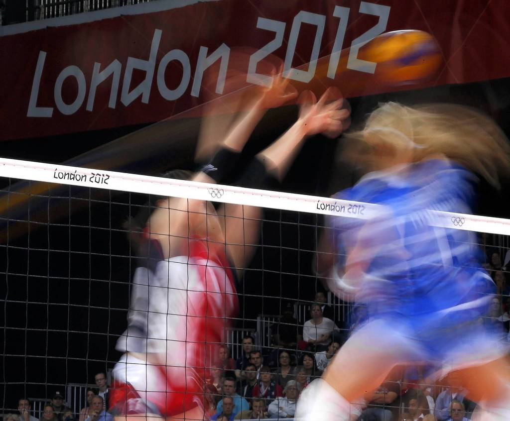 An Italian player spikes the ball against South Korea during their quarterfinal volleyball match at Earls Court.