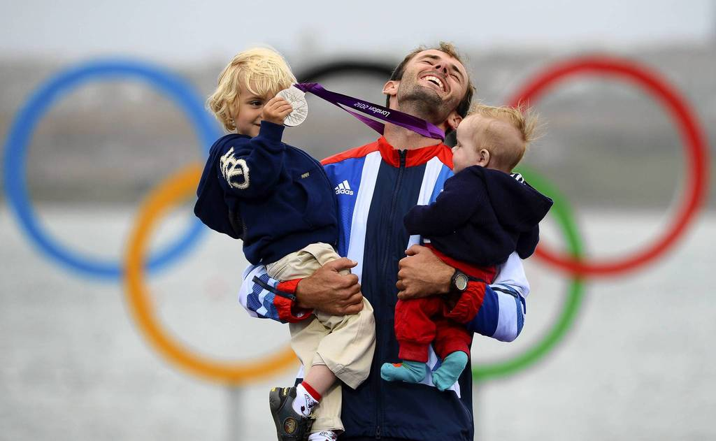 Britain's Nick Dempsey poses with his sons Thomas-Flynn and Oscar after he won silver in the men's RS:X sailing class.