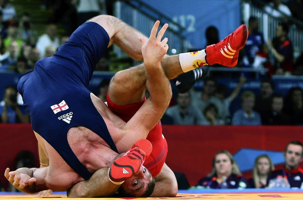 Hungary's Tamas Lorincz (back) wrestles Georgia's Manucher Tskhadaia during their 96 kg Greco Roman Wrestling semifinal match.
