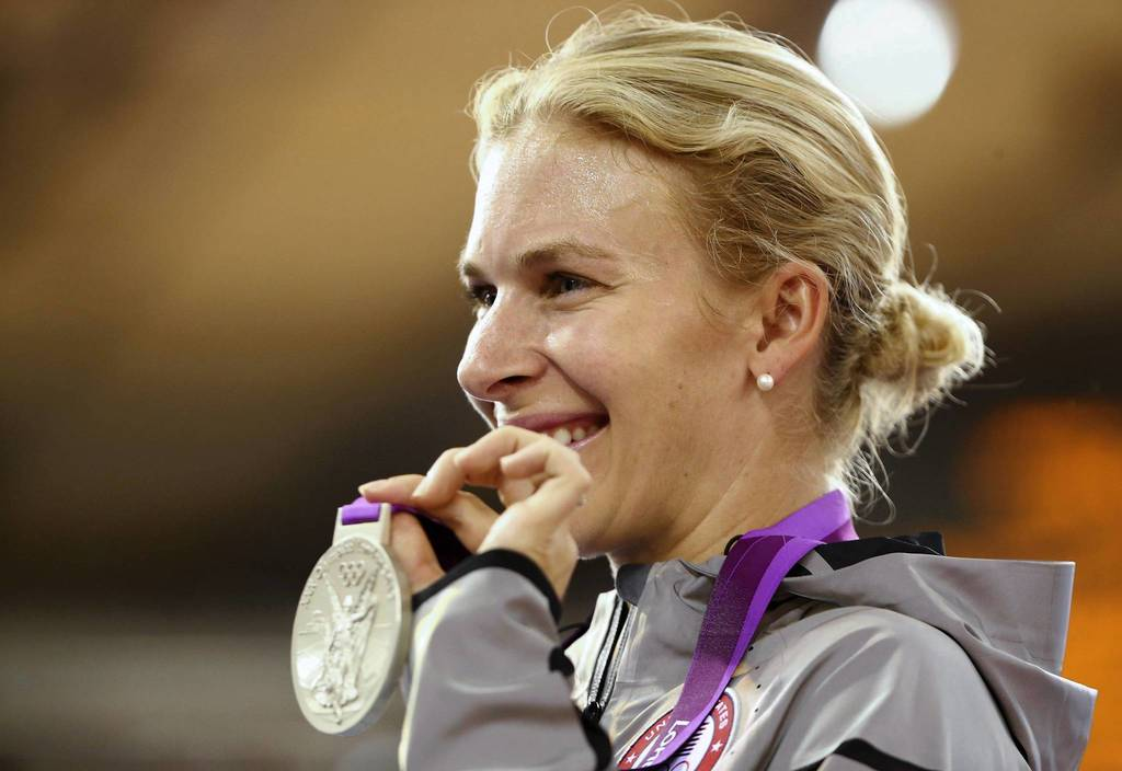 Silver medalist Sarah Hammer of the U.S. holds up her medal during the victory ceremony for the track cycling women's omnium at the Velodrome.
