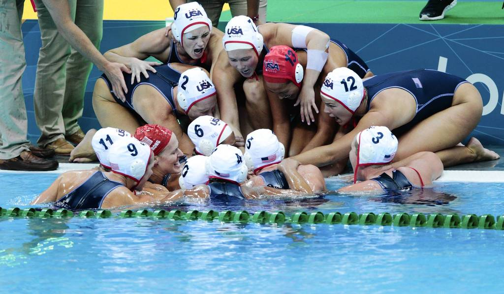 United States water polo players celebrate in a huddle after winning the semifinal match against Australia.