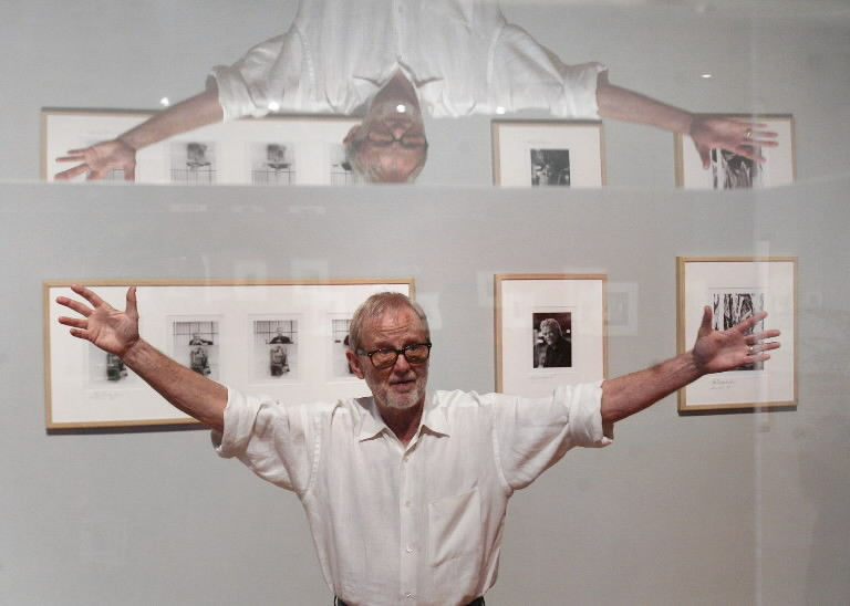 Jimm Roberts is reflected in a display case as he gives a tour of the exhibit of his portraits at Orlando Museum of Art.