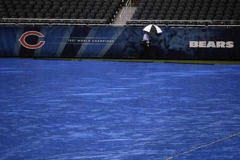 A rain shower falls on the tarp covering the Soldier Field turf.