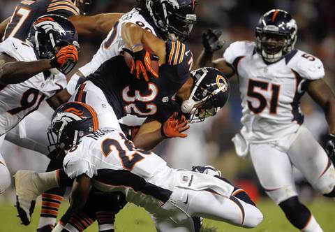 Running back Kahlil Bell is brought down by Broncos defensive back Rahim Moore in the first quarter.