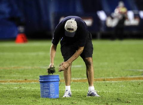 The grounds crew repairs the field at halftime.