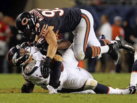 Defensive end Shea McClellin is called for a hit to the head as he and teammate Nate Collins pull down Broncos quarterback Caleb Hanie in the second quarter.