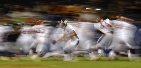 Broncos quarterback Adam Weber hands off in the fourth quarter.