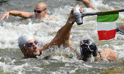 Italy's Valerio Cleri reaches up to grab a drink during the Men's 10km open water swimming marathon at the London 2012 Olympic Games.