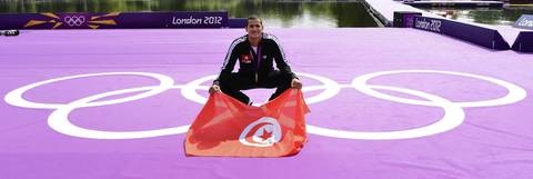 Oussama Mellouli holds a Tunisian flag as he poses with his gold medal after winning the men's 10km open water swimming marathon. Mellouli claimed victory to become the first person to win Olympic titles in both pool and open water races.