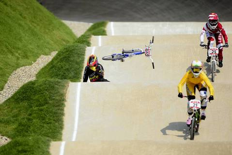 Venezuela's Stefany Hernandez comes off her bike as Australia's Lauren Reynolds (C) and Latvia's Sandra Aleksejeva (R) ride by during the BMX cycling women's semifinals event.