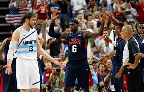 Lebron James celebrates with teammates as Argentina's Andres Nocioni complains to the official.