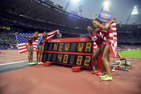 Carmelita Jeter, Bianca Knight, Tianna Madison and Allyson Felix celebrate next to the clock with their world record time after winning the women's 4x100m relay final.