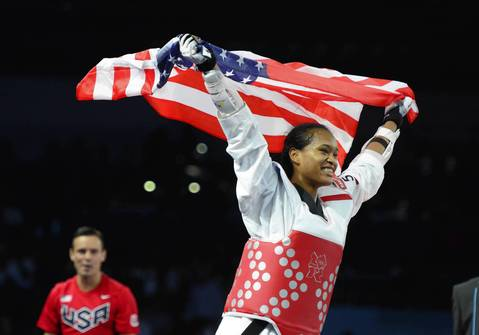 Paige McPherson celebrates with an American flag after defeating Franka Anic in the women's 67kg bronze medal final.