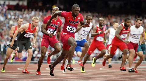 Justin Gatlin, of the United States, reaches back for the baton from teammate Trell Kimmons, third from left, during heat 2 of the men's 4X100m relay.