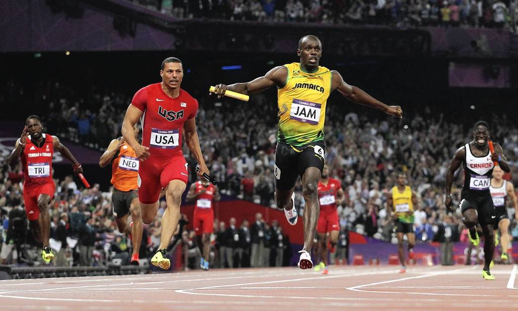 Usain Bolt of Jamaica crosses the finish line ahead of Ryan Bailey of the United States to win gold and set a new world record of 36.84 during the Men's 4 x 100m relay final.