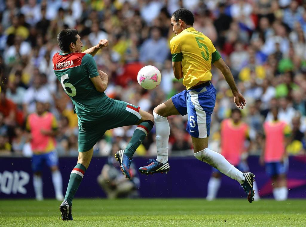 Hector Herrera of Mexico (L) and Sandro of Brazil battle for the ball during the Men's Football Final between Brazil and Mexico.