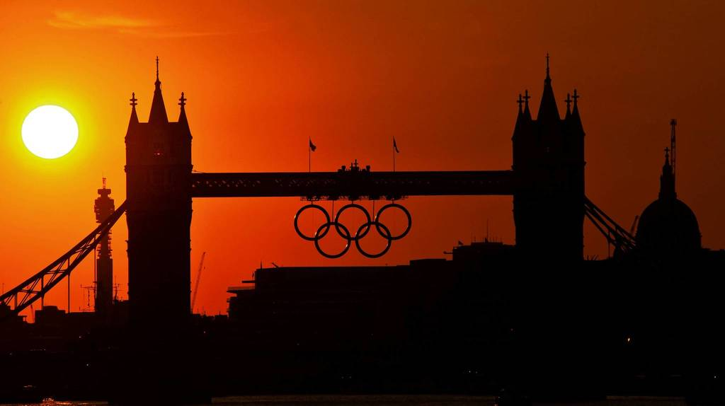 The sun sets behind the 2012 London Olympic Rings on Tower Bridge in London.