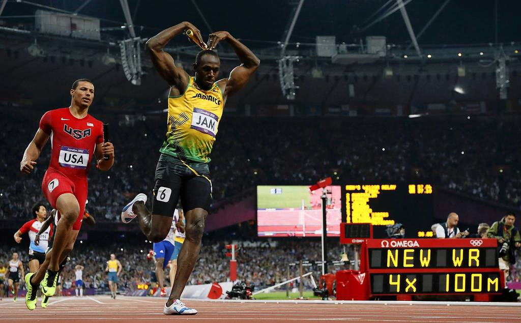 Jamaica's Usain Bolt celebrates after crossing the finish line on the anchor leg to set a world record in the men's 4x100m relay final ahead of Ryan Bailey of the U.S.