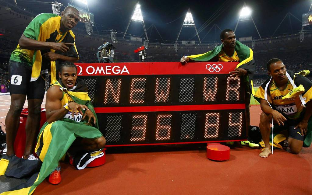 Jamaica's Usain Bolt, Yohan Blake, Nesta Carter and Michael Frater pose next to their new world record of 36.84 seconds after winning the men's 4x100m relay final.