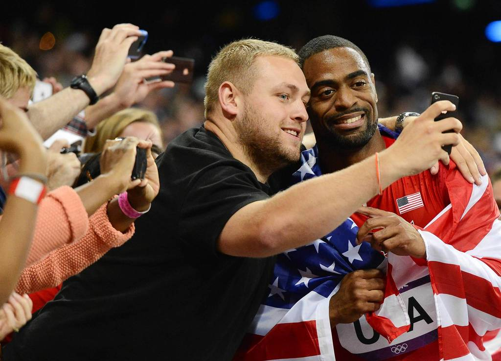 U.S. sprinter Tyson Gay celebrates with fans in the stands after taking silver in the men's 4x100m relay final.