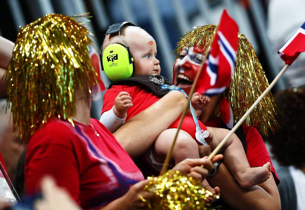 A supporter of Norway cheers with her baby during the women's gold medal handball match against Montenegro at the Basketball Arena.