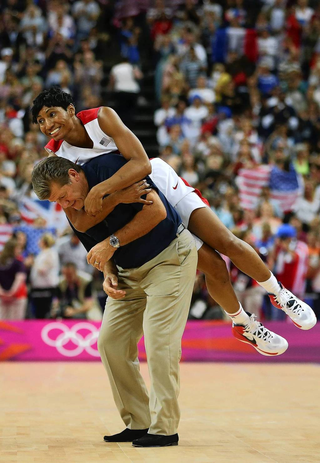 Angel McCaughtry jumps on the back of coach Geno Auriemma after the U.S. women's basketball team defeated France 86-50 to win the gold medal.
