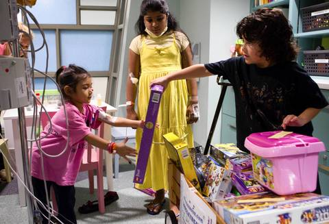 Acey Longley distributes toys to patients Moriah Cueva, 4, left, and Amira Dadar, 10.