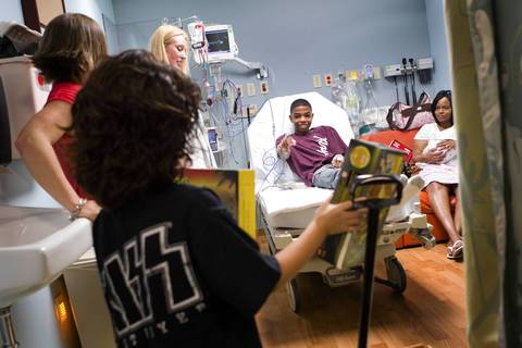 Antione McDonald, 16, chooses his gift as Acey Longley distributes toys to patients at Edward Hospital in Naperville.