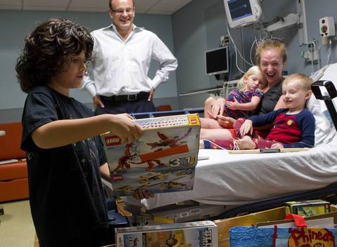 The Dee family reacts as Acey Longley gives them toys at Edward Hospital in Naperville. Acey turns 9 on Sunday, Aug. 12.