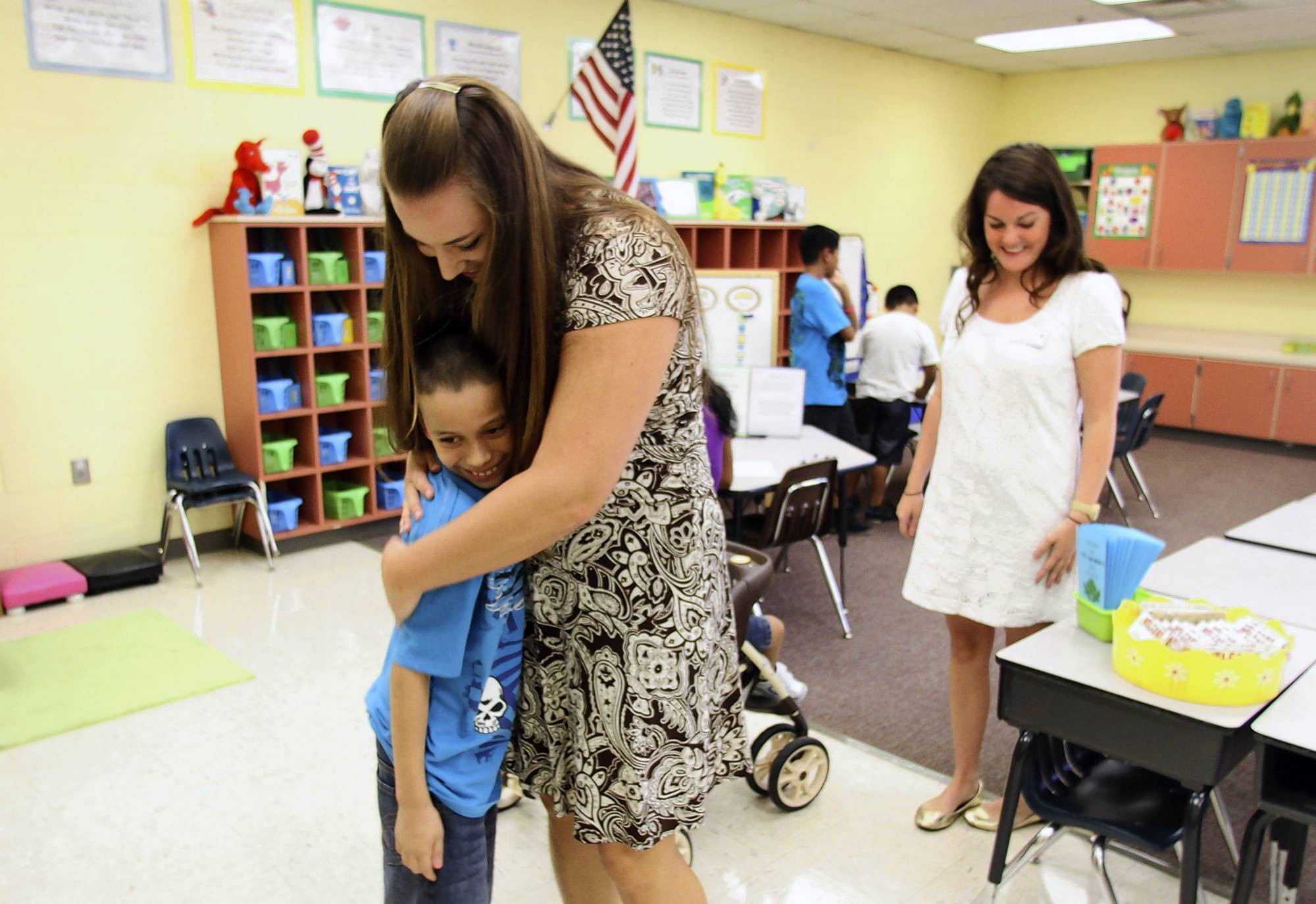 Kevin Penate, 10, gets a hug from his former first-grade teacher Kristina Gardner at Wicklow Elementary in Sanford. At right is UCF intern Sara Gagliardi.