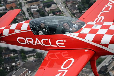 Aerobatic pilot Sean D. Tucker, left, flies Chicago firefighter Steve O'Malley, who rescued a baby from drowning at the 31st Street Harbor Aug. 4, in Team Oracle's Extra 300 airplane, during media preview day for the Chicago Air & Water Show at the Gary Jet Center.