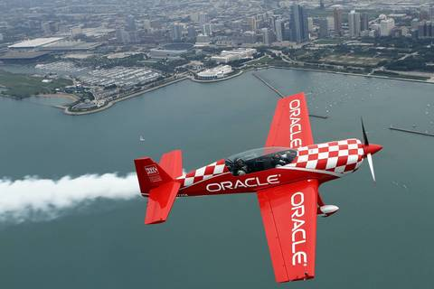 Aerobatic pilot Sean D. Tucker flies Chicago firefighter Steve O'Malley, who rescued a baby from drowning at the 31st Street Harbor Aug. 4, in Team Oracle's Extra 300 airplane, during media preview day for the Chicago Air & Water Show at the Gary Jet Center.