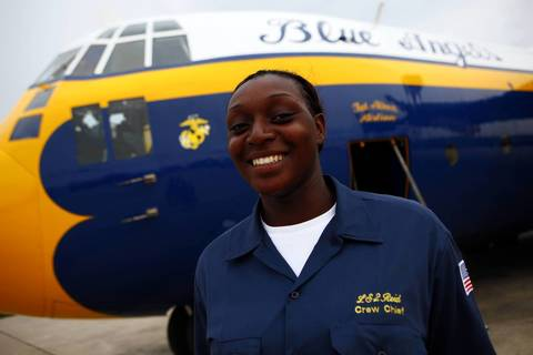 """Navy Logistics Specialist 2nd Class Vania Reid, 22, stands with the Blue Angels' C-130 transport airplane nicknamed """"Fat Albert"""" at the Gary Jet Center in Gary, Ind."""