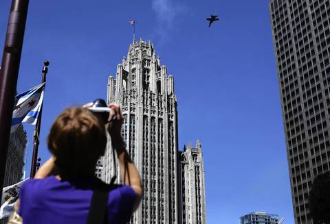 Pedestrians and tourists try to catch a glimpse of the airplanes flying over the city as a dress rehearsal for the 54th annual Chicago Air and Water is held.