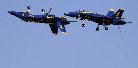 With landing gear deployed on their F-18 Hornets, the Blue Angels perform during dress rehearsal for the Chicago Air and Water Show.