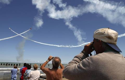 People snap photos from North Avenue Beach as a dress rehearsal is held for the Chicago Air and Water Show.