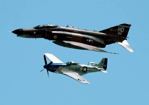 A vintage F-4 Phantom fighter jet and a WWII-era P-51 Mustang fly in formation during rehearsal for the Chicago Air and Water Show.