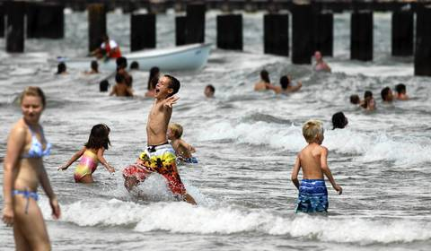 Kids swimming at North Avenue Beach didn't seem to be distracted by the high-performance aircraft overhead as they enjoyed the water of Lake Michigan.