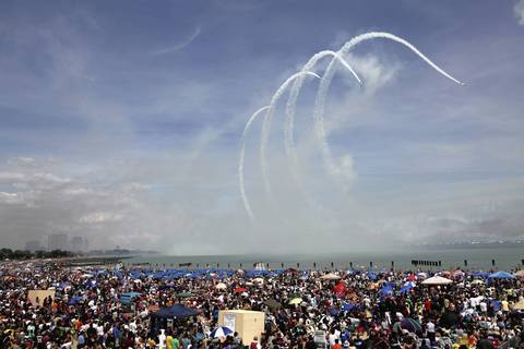 The Aeroshell flight team performs maneuvers over Lake Michigan as the crowd on North Avenue Beach watch.
