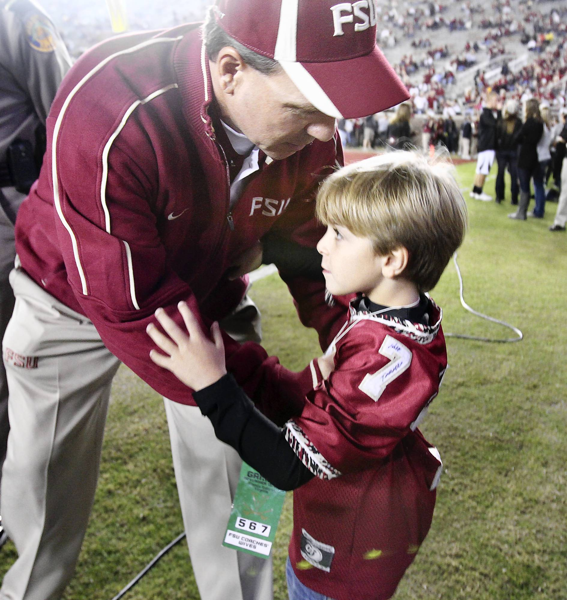 FSU head coach Jimbo Fisher reaches to hug his son, Ethan, on the field before the start of the Virginia at Florida State game in Tallahassee in November. (Stephen M. Dowell/Orlando Sentinel file)