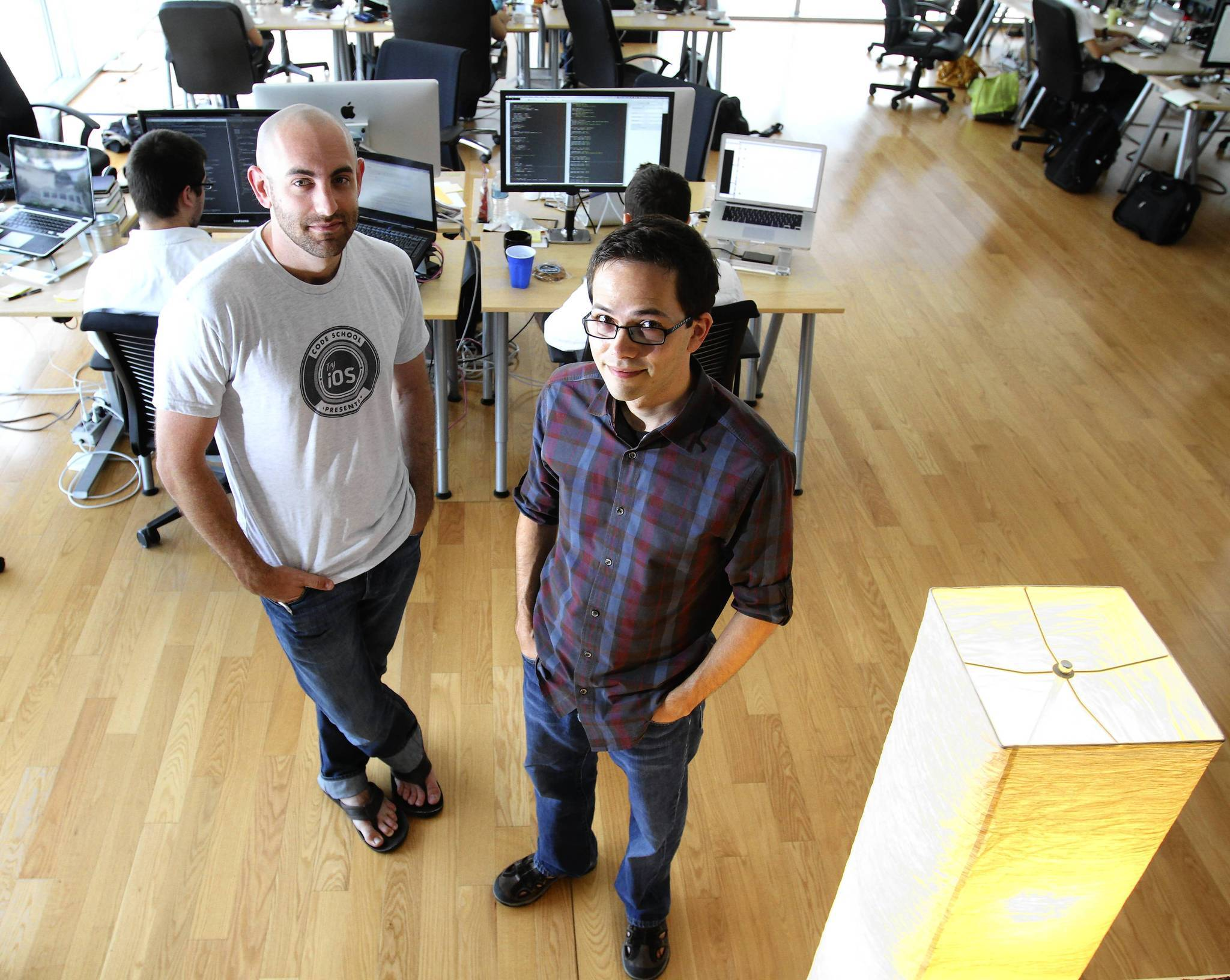 Eric Allam, left, and Gregg Pollack, at Envy Labs Code School in the Plaza in downtown Orlando, seek funding for Try iOS. (Joe Burbank, Orlando Sentinel)