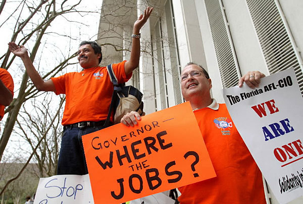 Lynx bus driver Tom Colon, of Orlando, holds signs with OIA shuttle bus driver Ismael Blanco, as demonstrators from around the state rally in front of the Florida Capitol in Tallahassee, Wednesday, March 9, 2011, to protest proposed cuts in unemployment compensation.